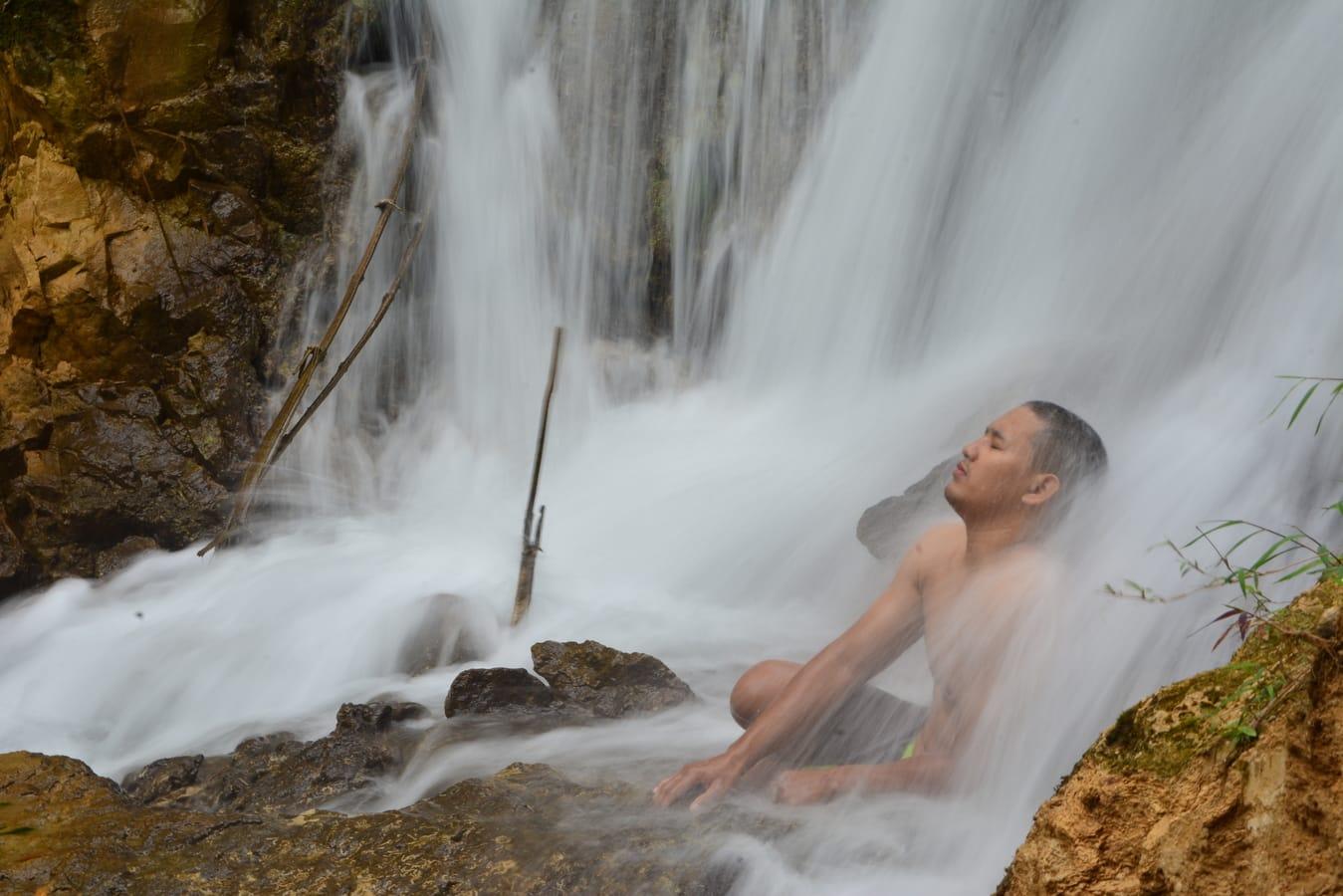 Wodospad Yogyakarta mezczyzna siedzacy pod wodospadem zen